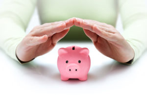 protect your savings - with his hands covering the piggy bank